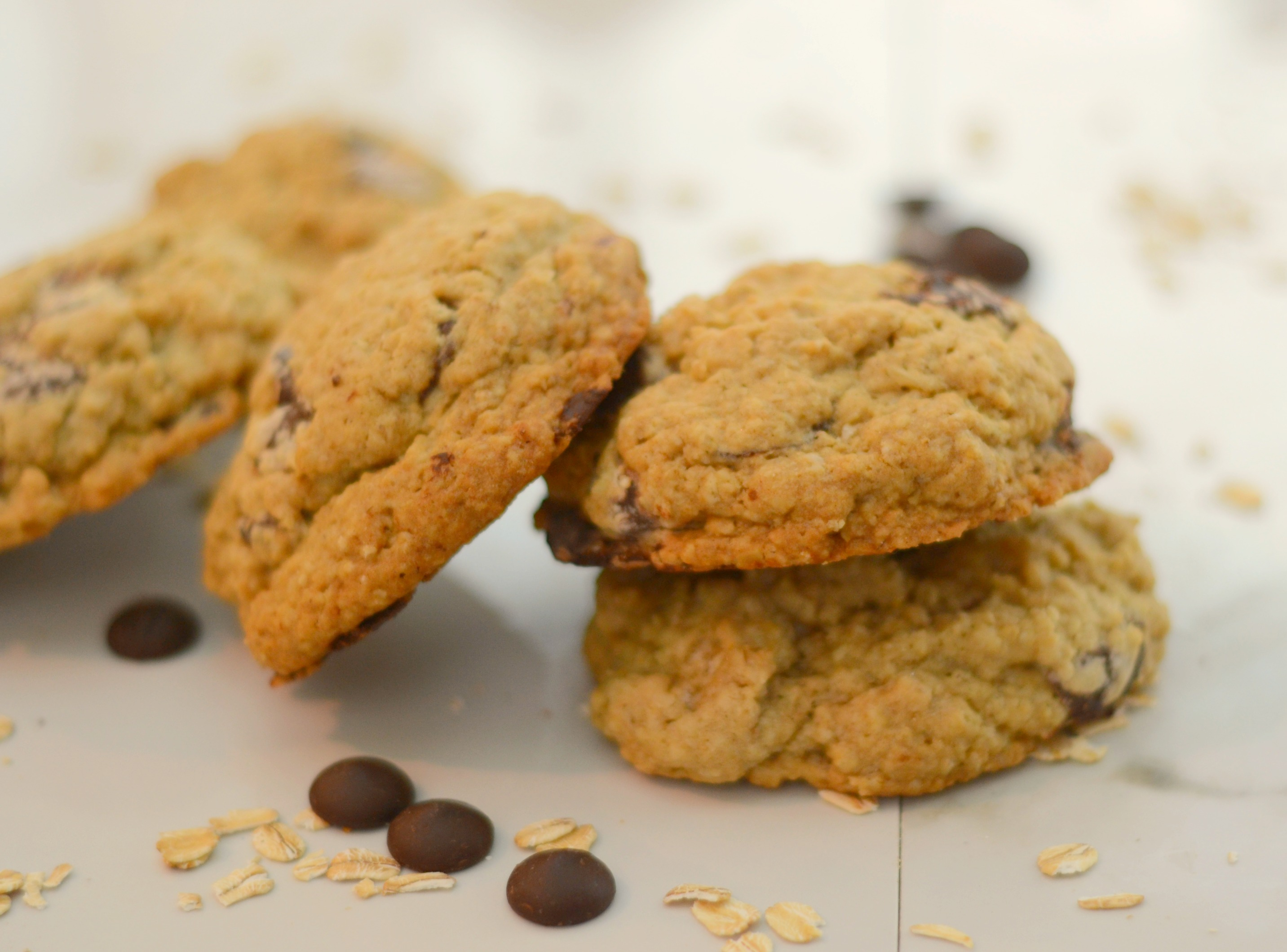 a toppled stack of oatmeal chocolate chip cookies on a white background