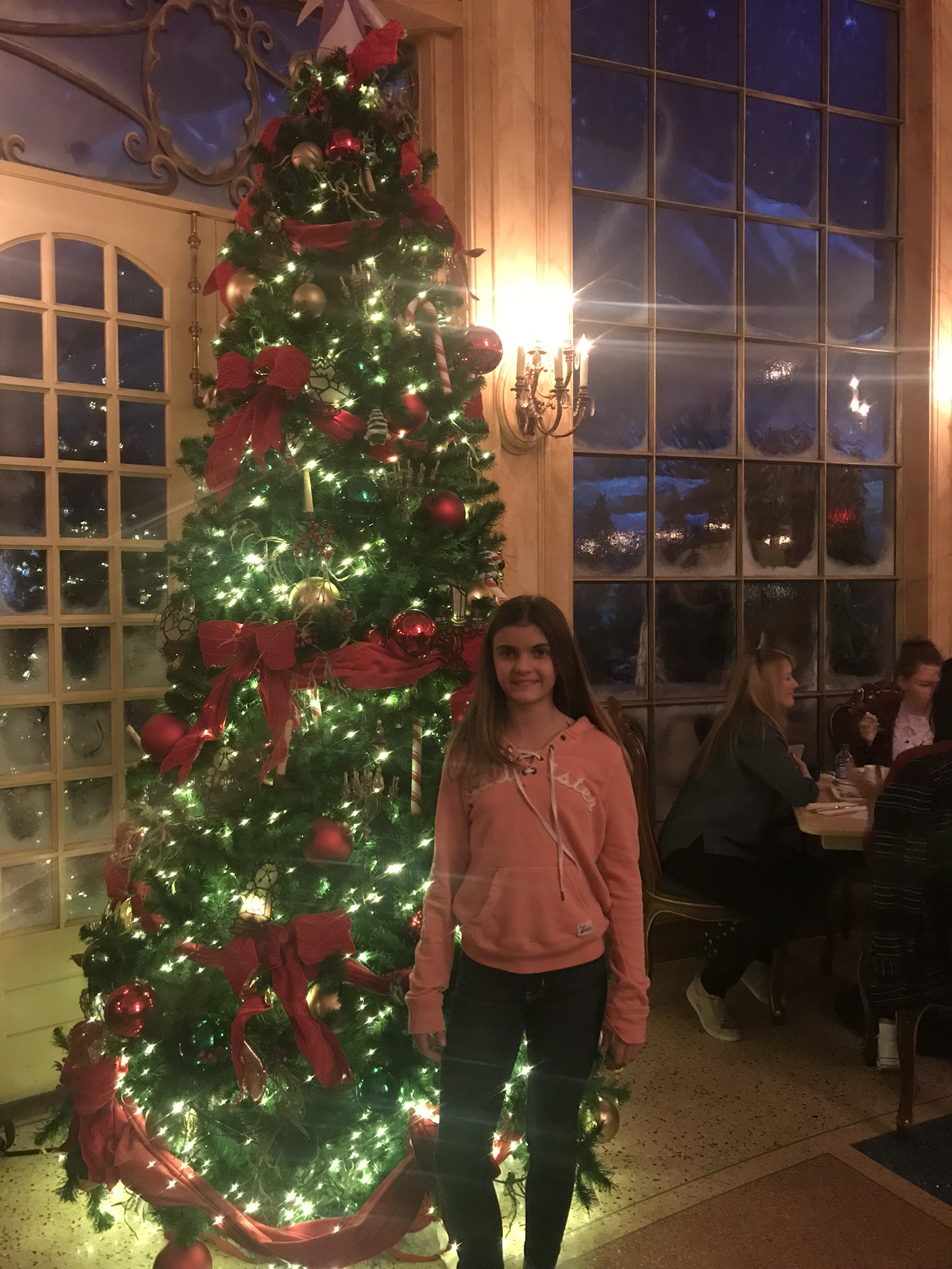Girl standing in front of Christmas tree in the Grand Ballroom of the Be Our Guest Restaurant at Disneyworld's Magic Kingdom