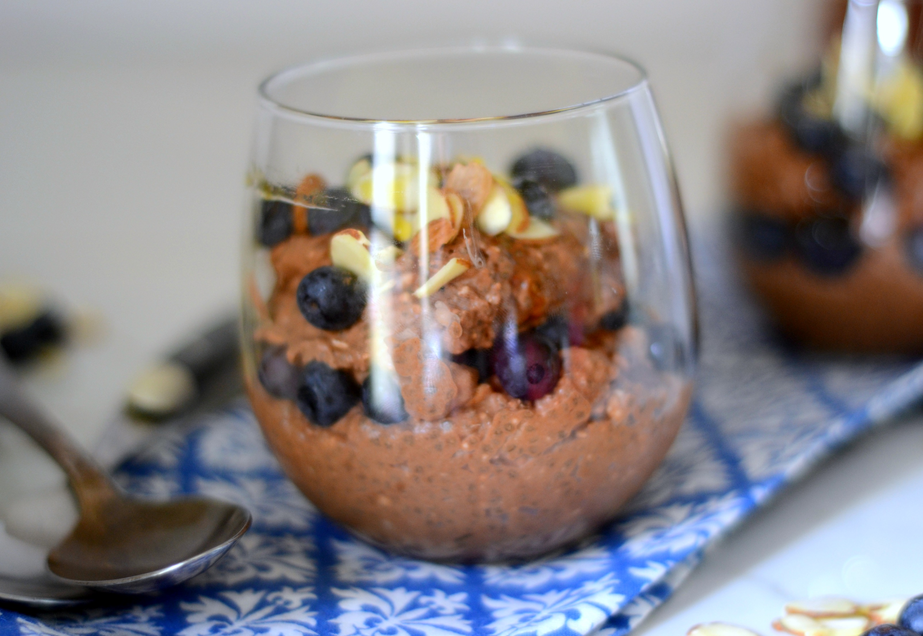 glass dish filled with chocolate chia pudding topped with slivered almonds and blueberries