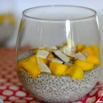 glass full of chia pudding topped with mango and dried coconut
