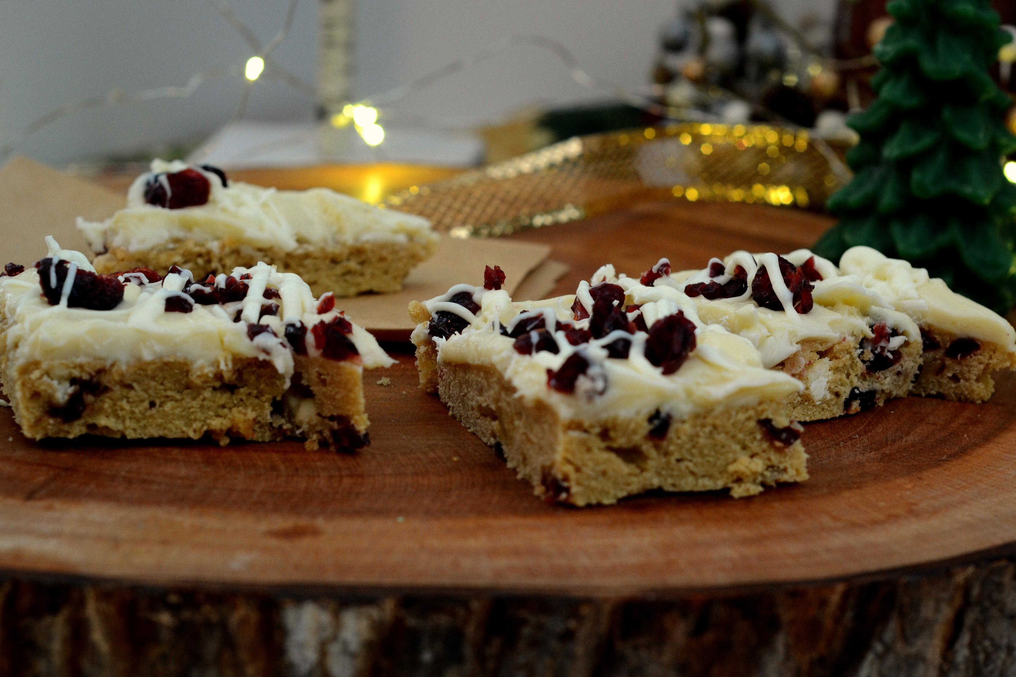 White Brownies with Frosting with Cranberries and a drizzle of white chocolate, holiday decorations in the background
