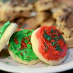 A plate of festive holiday cookies, featuring red and green soft sugar cookies with Christmas sprinkles.
