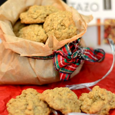 brown paper bag with mini oatmeal cookies pouring out of it surrounded by Christmas decorations