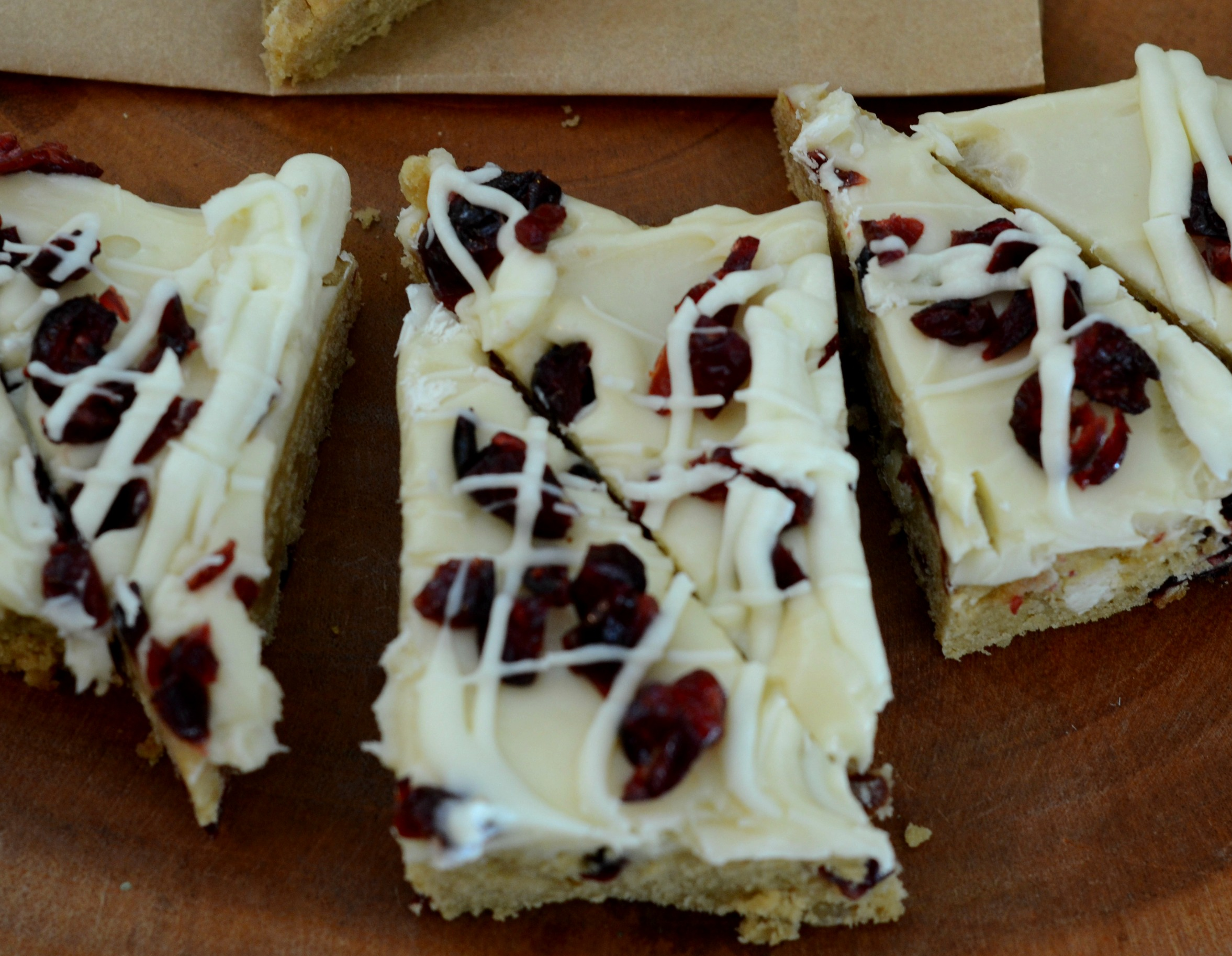 Overhead view of white chocolate blondies covered with cream cheese frosting, cranberries and a white drizzle.