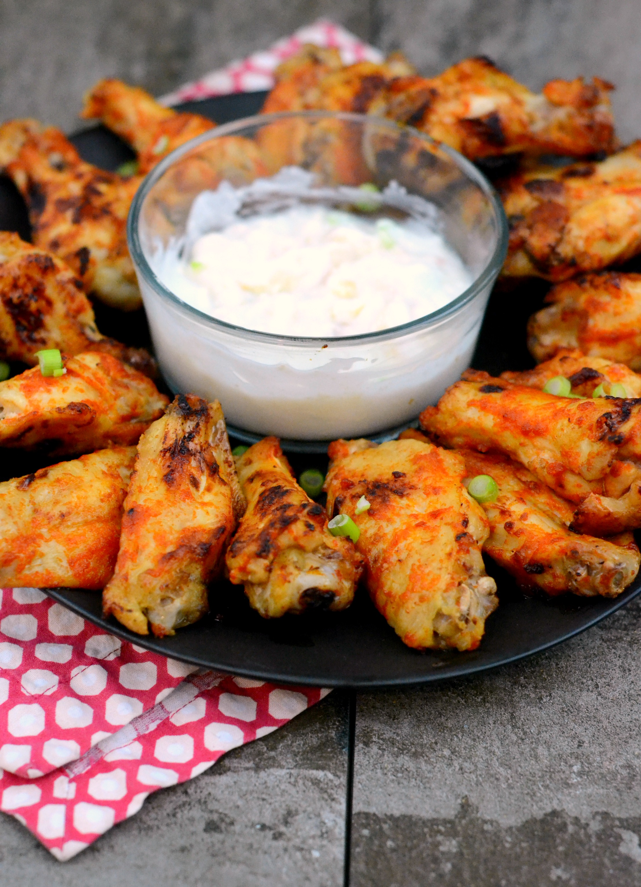Spicy baked paleo wings arranged in a circle with a dipping sauce in the middle.