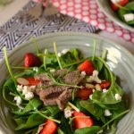 bowl of spinach and other greens topped with strawberries, steak and goat cheese
