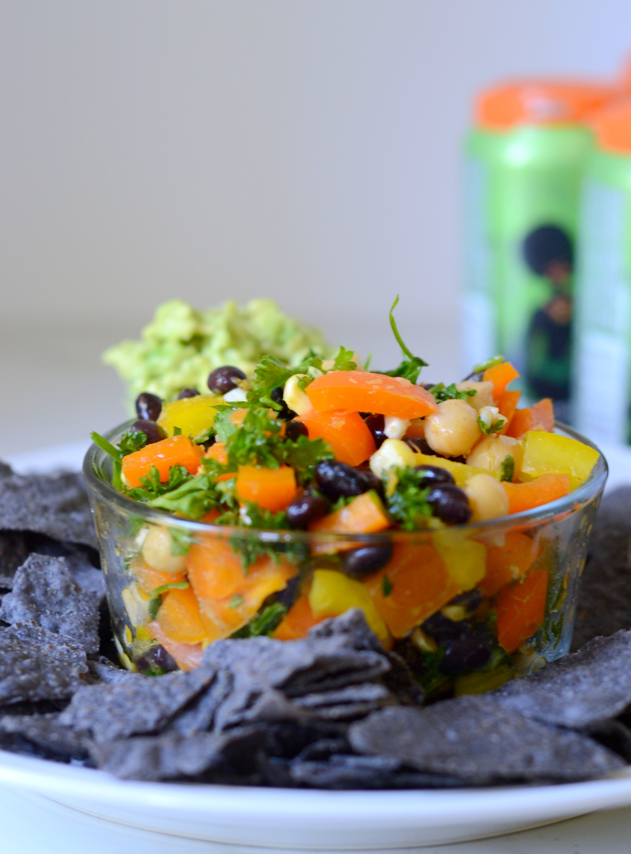 Bowl of Puerto Rican Bean Salad with blue tortilla chips and beer