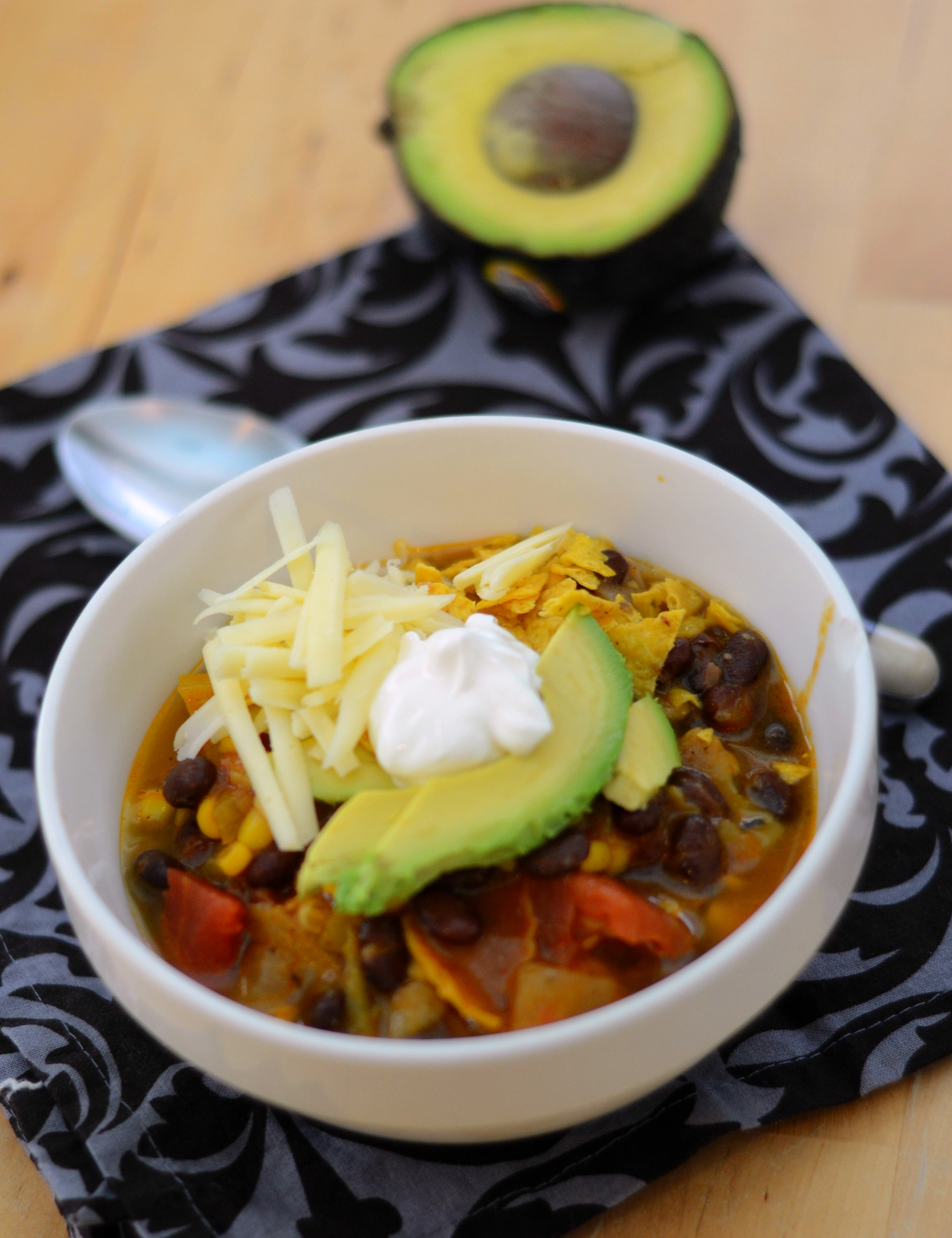 Bowl of Vegetarian Tortilla Soup topped with avocados, cheese and sour cream