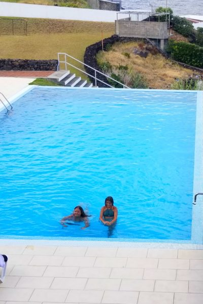 mom and daughter swimming in infinity pool in azores islands