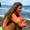 girl sitting on surfboard on beach in Sao Miguel Azores