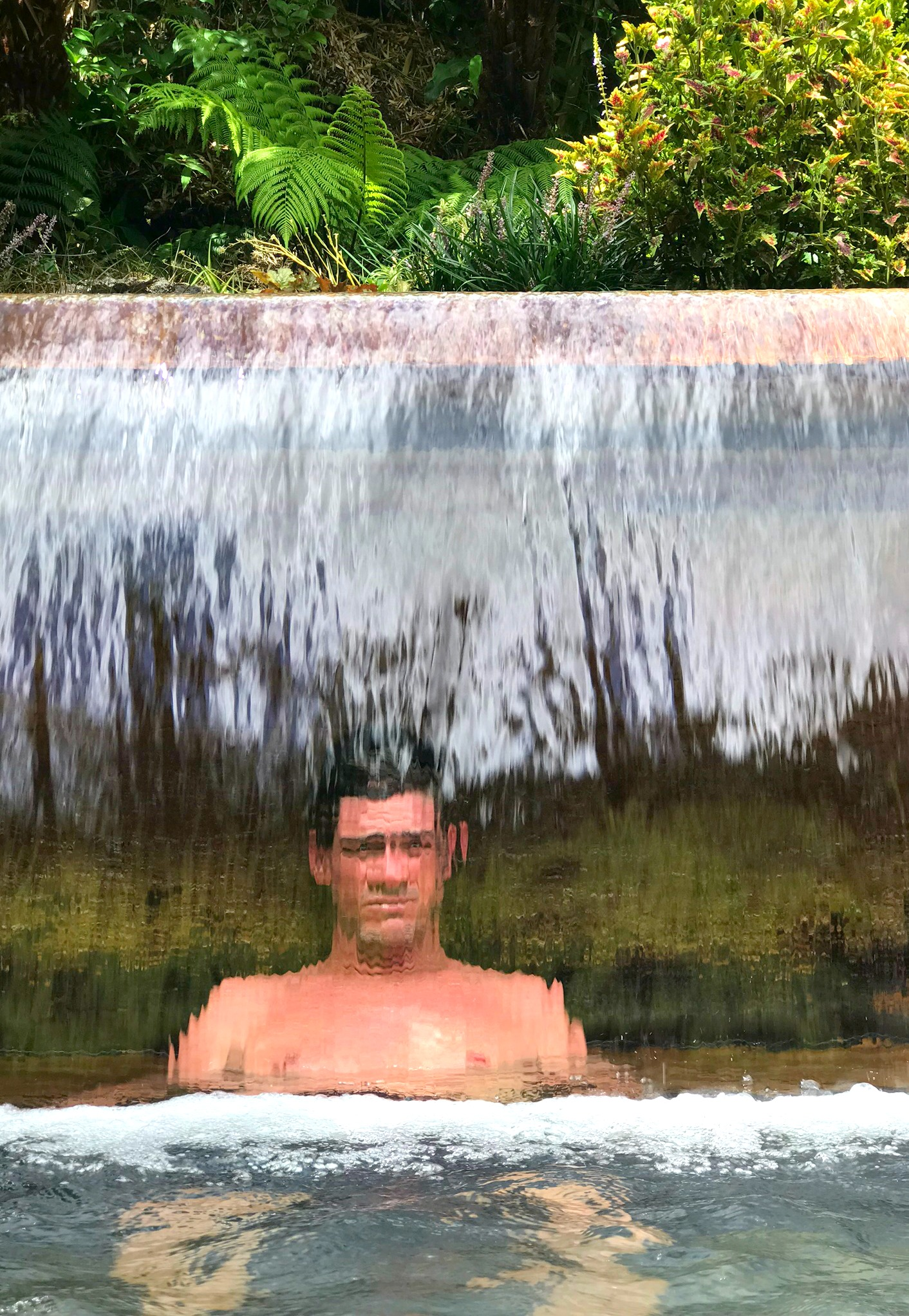 man sitting in hot spring behind waterfall
