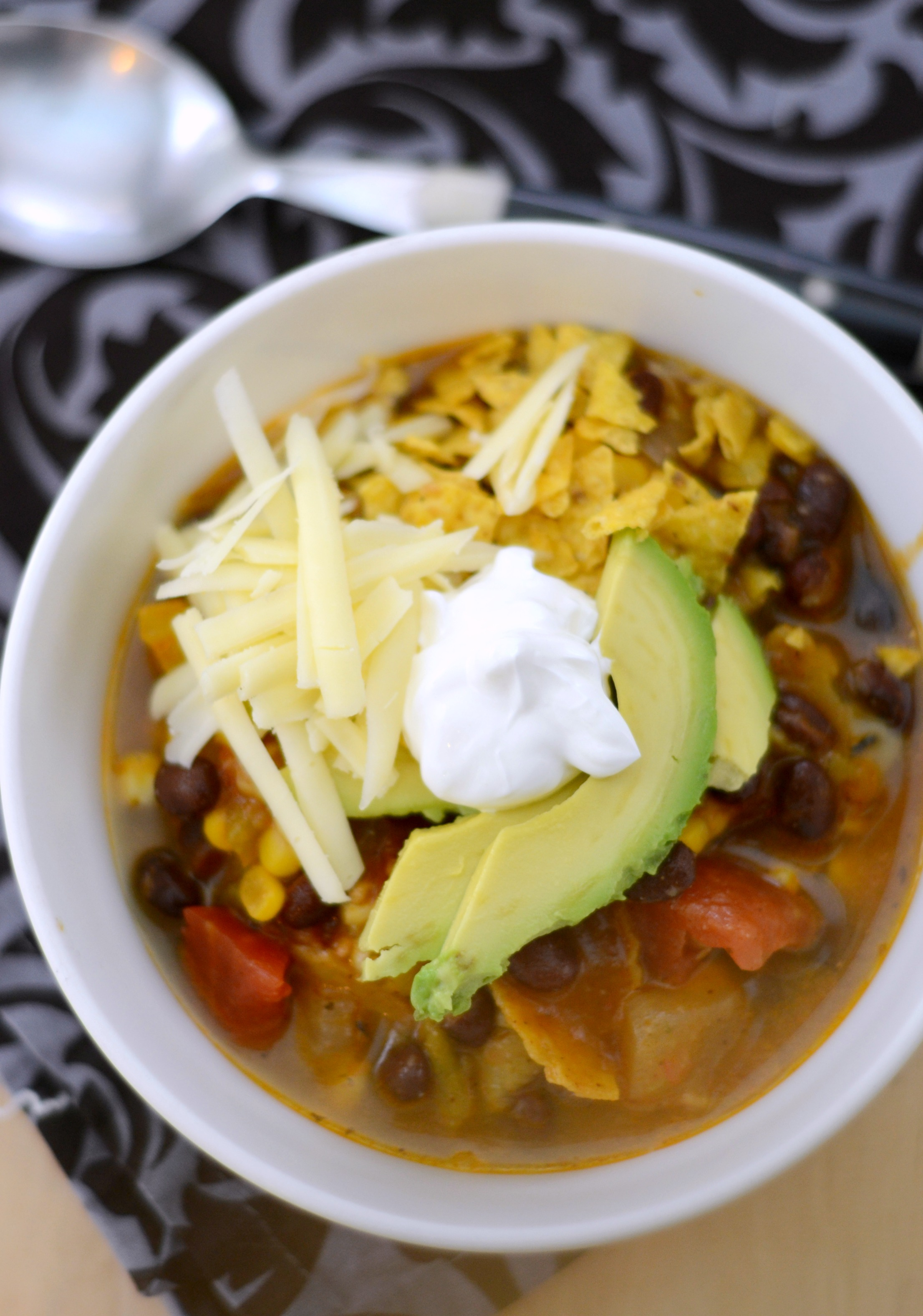 Overhead view of a bowl of vegetarian tortilla soup topped with sour cream, cheese and avocados
