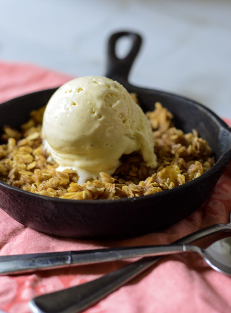 cast iron pan with peach crisp topped with vanilla ice cream