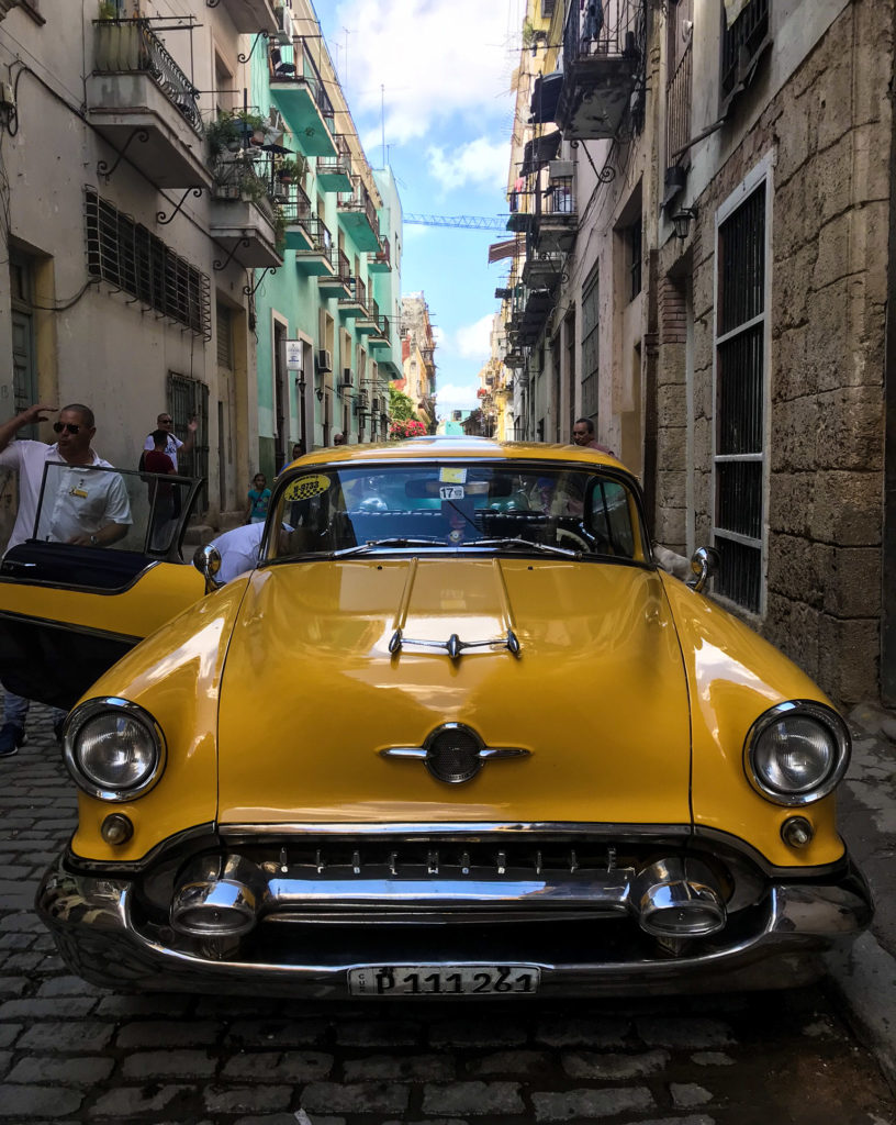 Havana Cuba small street with vintage yellow car in the foreground