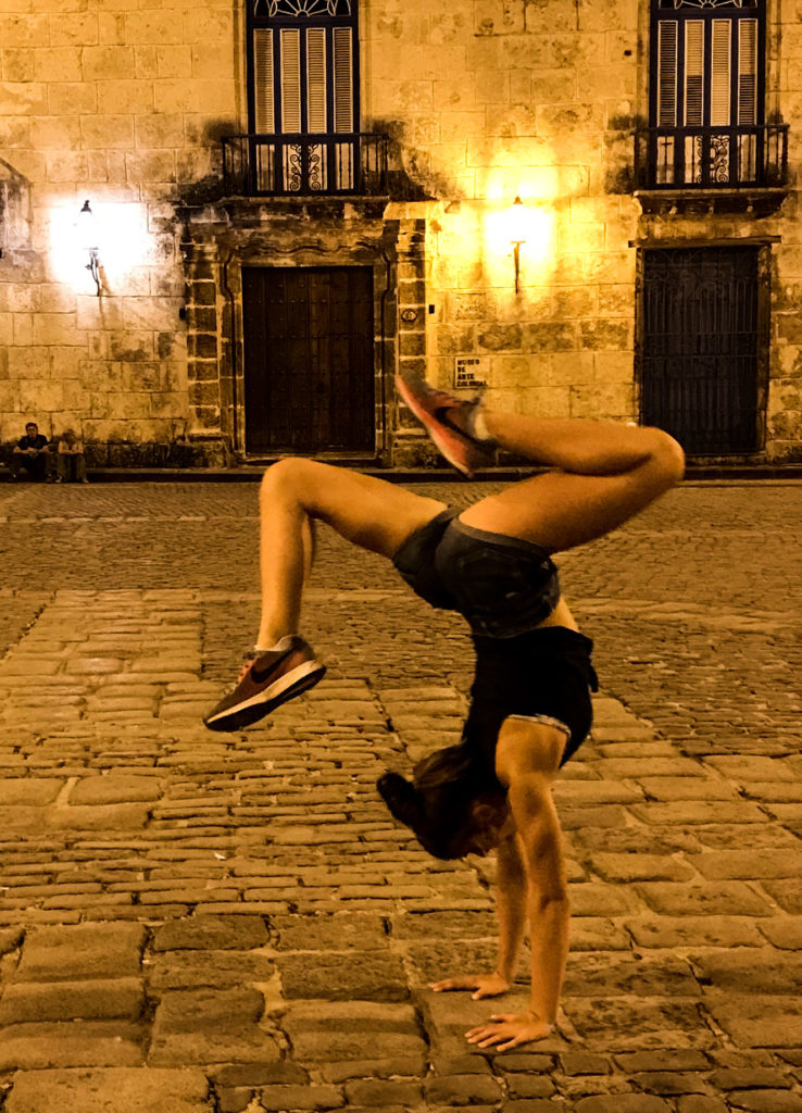 Girl doing a stag handstand in Old Havana, Cuba at night