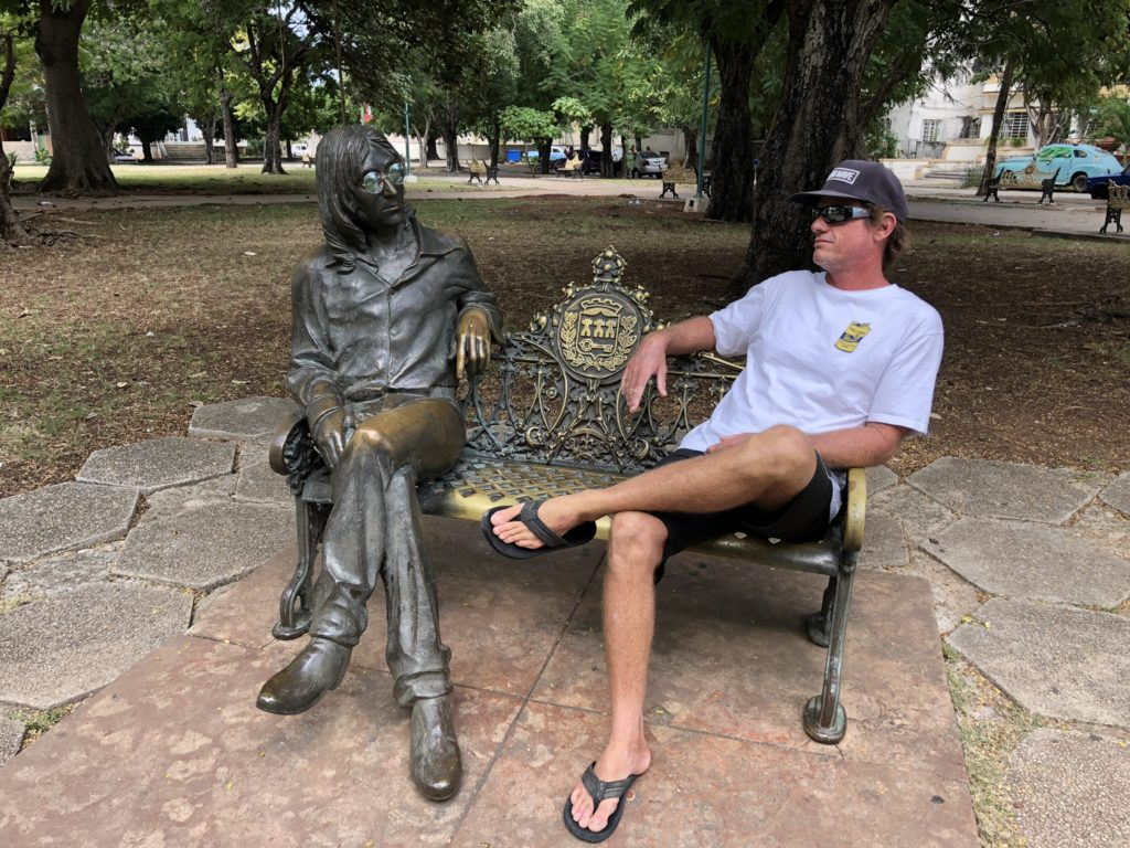 Man sitting in Havana Cuba park next to John Lennon statue