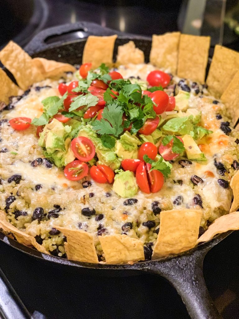 Chipotle Black Beans and Cilantro Rice Bake in a cast iron pan and topped with cheese, tomatoes, and avocados