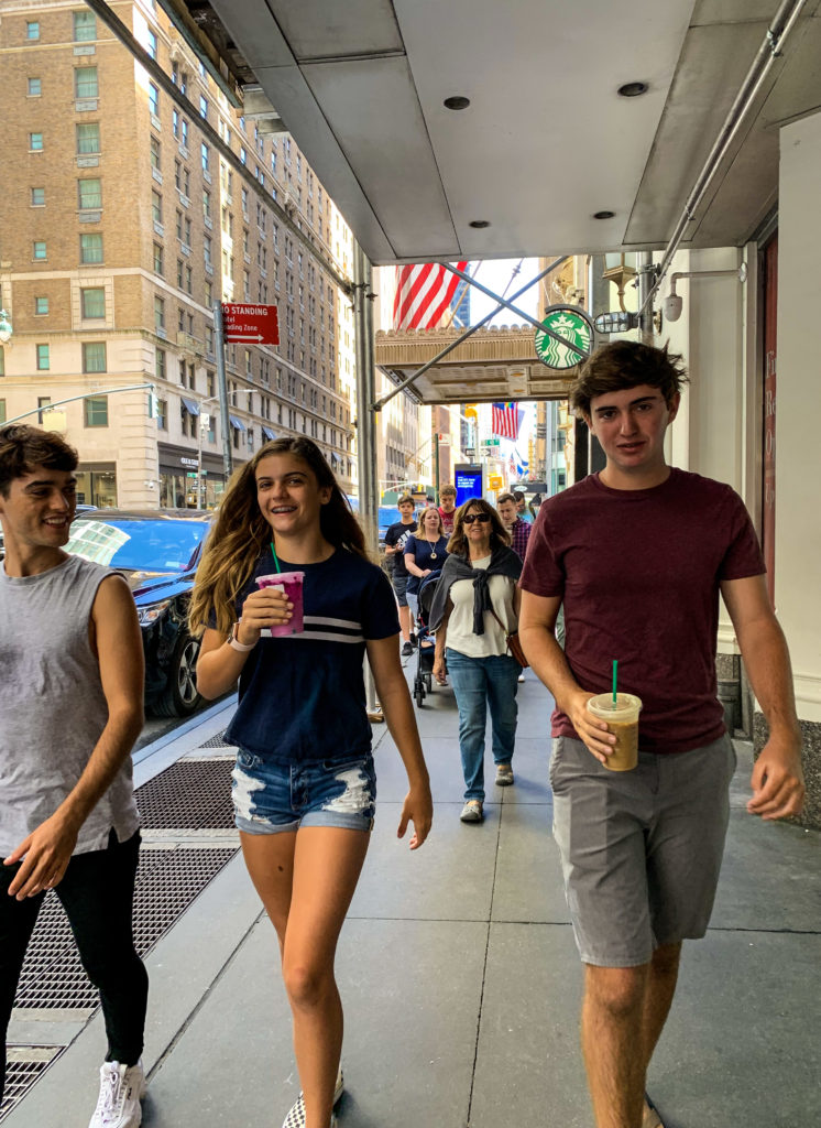 three teens walking the streets of New York City with Starbucks