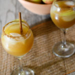 two wine glasses with apple cider mocktail with apples in the background